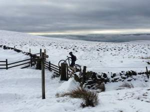 A mountain biker near Lose Hill in the Peak District carries their bike over a blanket of snow.